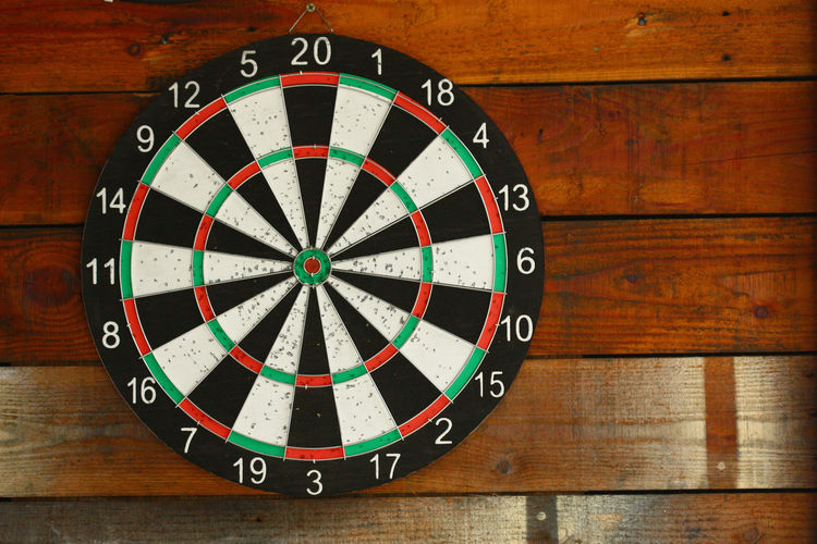 Close-up of dartboard on wooden wall