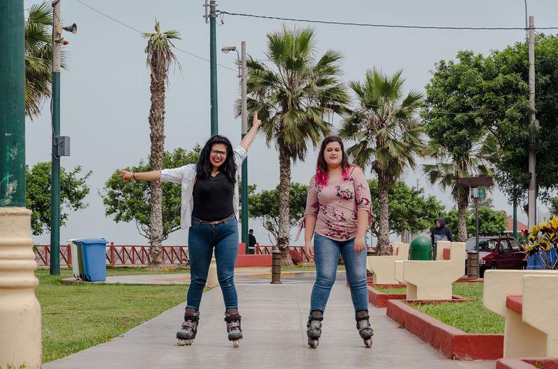 Portrait of happy friends skateboarding on footpath in park