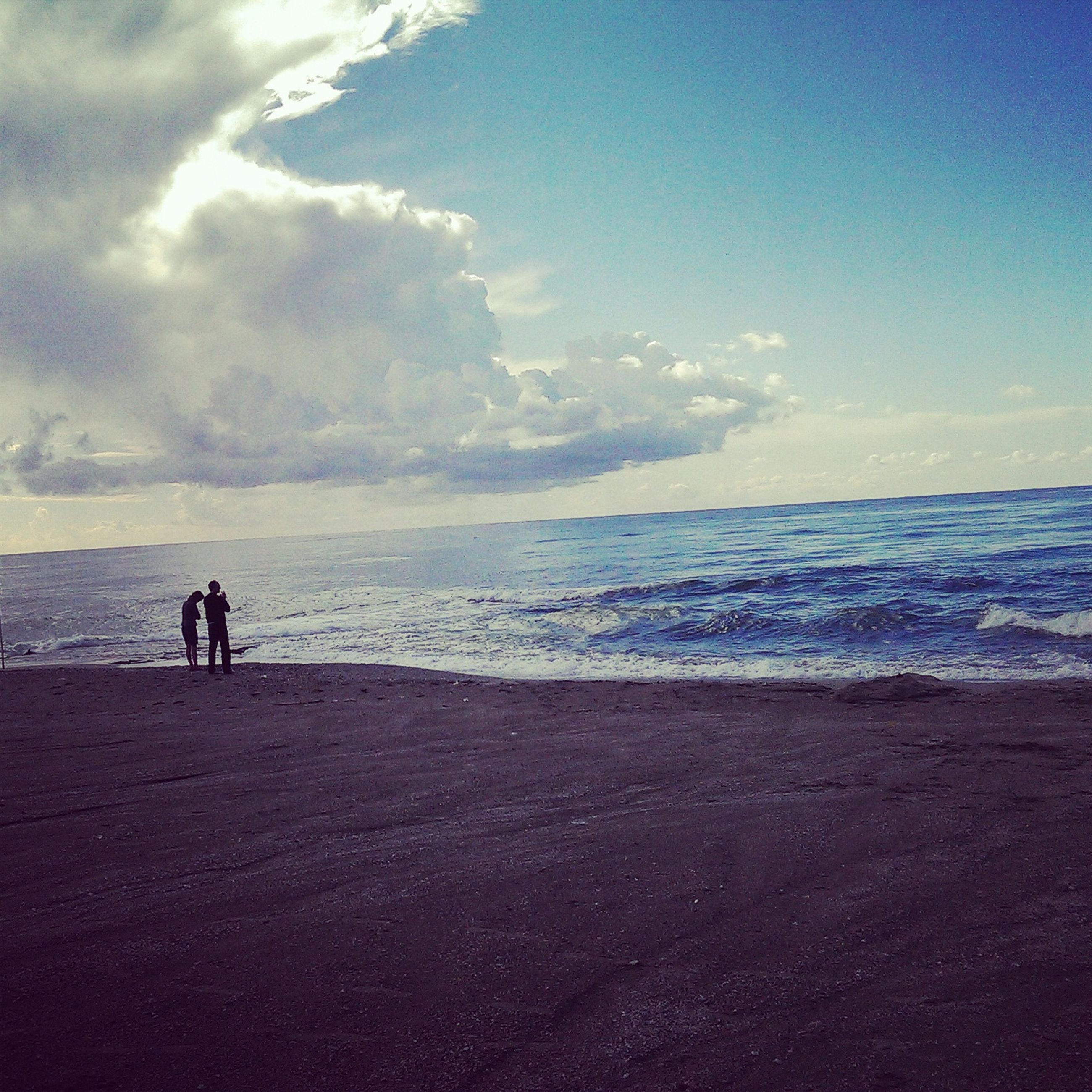 sea, horizon over water, beach, water, sky, lifestyles, leisure activity, scenics, shore, men, tranquil scene, beauty in nature, full length, tranquility, cloud - sky, vacations, nature, silhouette