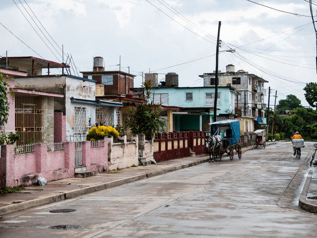 Holguin, Cuba - September 2017: Typical street in Holguin. Horse and carriage transportation. 3rd World Cuba Horse And Carriage Life Living Poverty Lives. Weathered Architecture Buggy Caribbean Cloud - Sky Colorful Cuban Day Embargo Island Lifestyles Neglect Poverty Power Line  Security Bars Third World Tropical Climate Worn Worn Down EyeEmNewHere