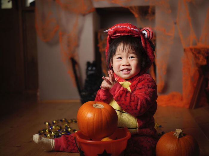 Portrait of cute baby girl in halloween costume sitting at home