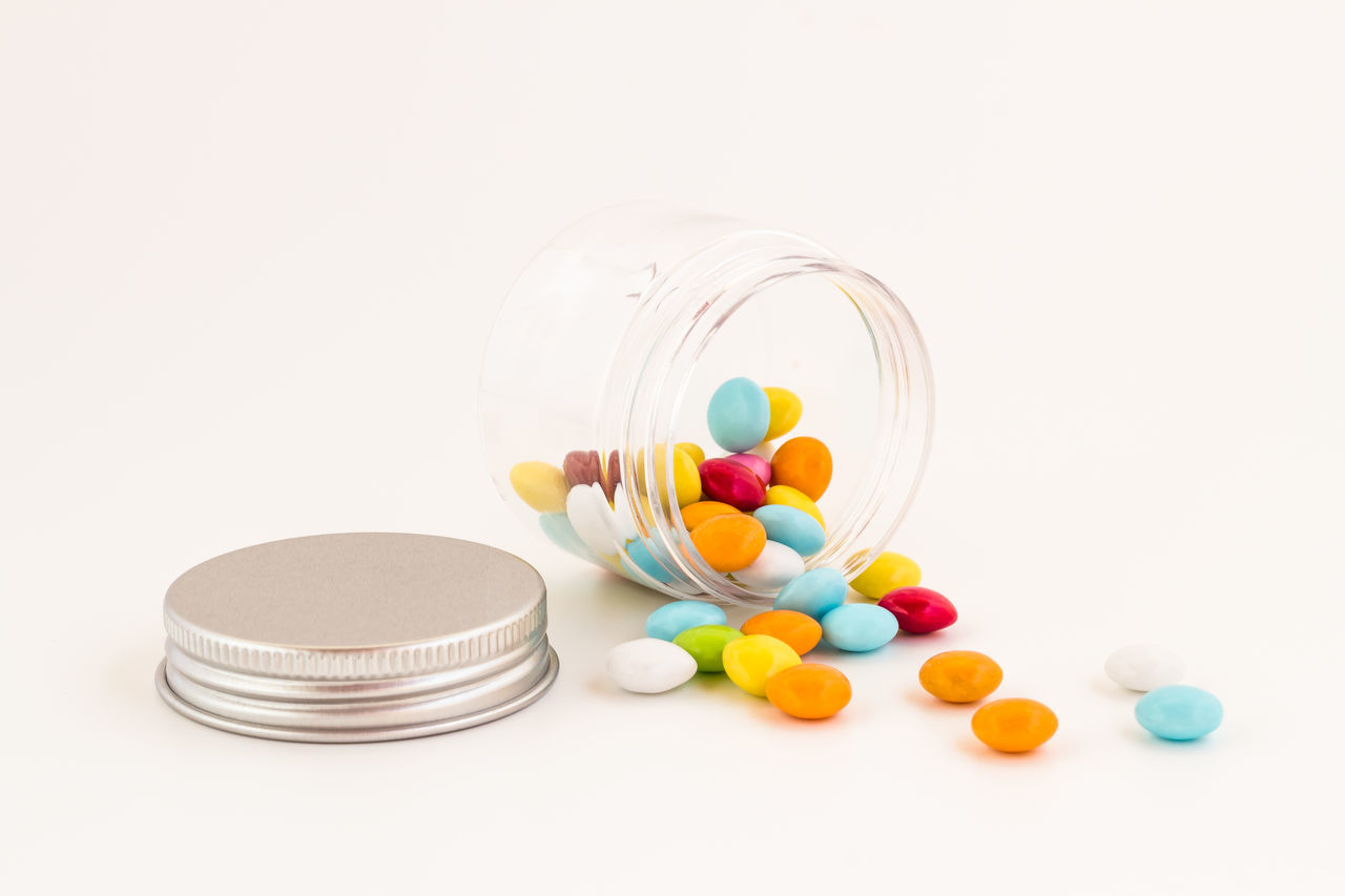 white background, studio shot, copy space, healthcare and medicine, no people, multi colored, pill, medicine, close-up