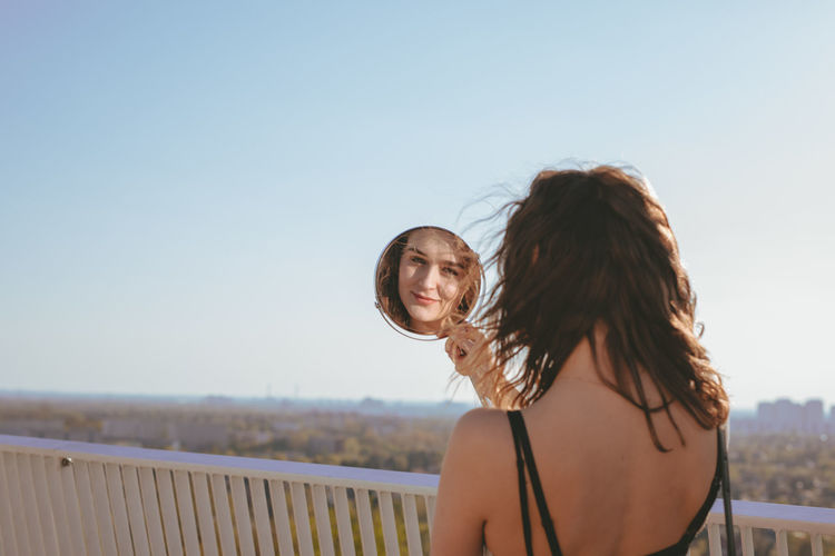 Rear view of young woman looking in mirror against clear sky
