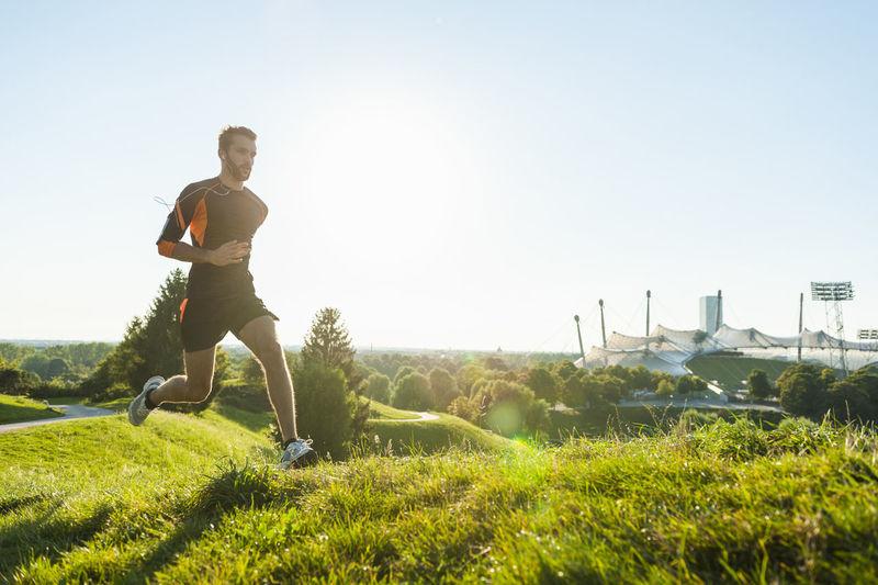 Full length of man running on grass against sky