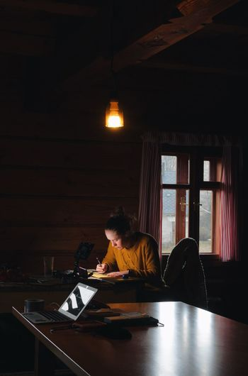 female artist painting a picture with watercolour in a cozy wooden cabin Artist At Home Creativity DIY Females Illustrator Romantic Student Woman Working Artowrk Brush Cabin Cottage Cozy Creative Drawing Handmade Illustration Indoors  Lodge Painting Real People Sky Table