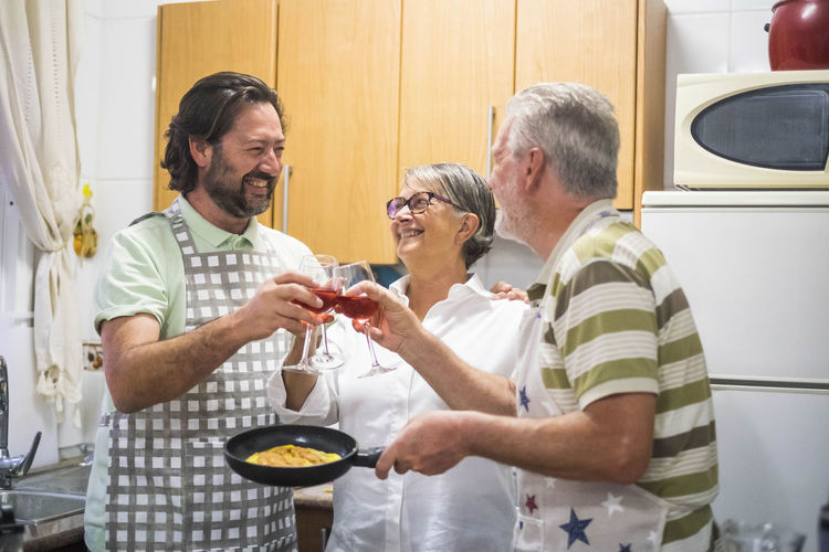 Smiling Son Toasting Wineglasses With Parents In Kitchen At Home