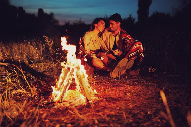 Man And Woman Sitting By Campfire At Night