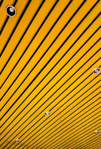 Low angle view of yellow striped ceiling with recessed lights