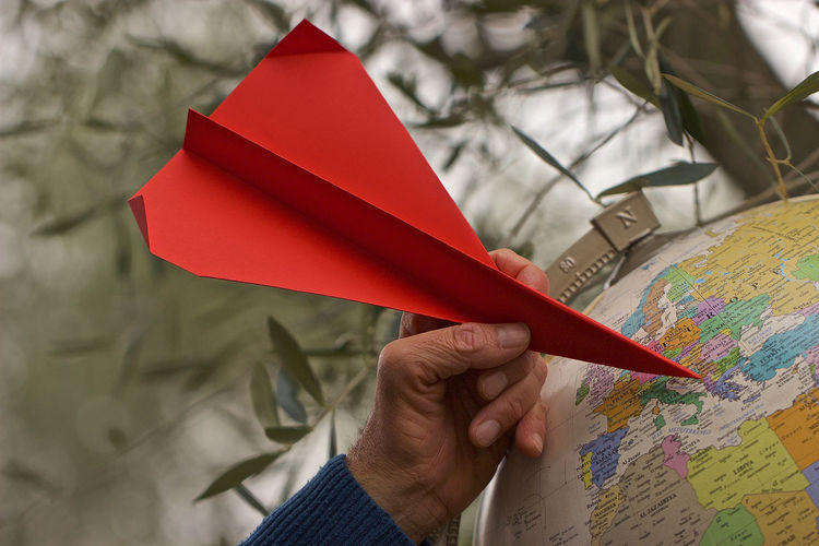 Cropped hand holding red origami on globe