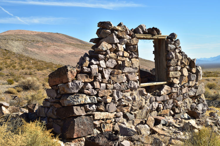 Deteriorating wall with one remaining window frame of stone house in nevada desert ghost town