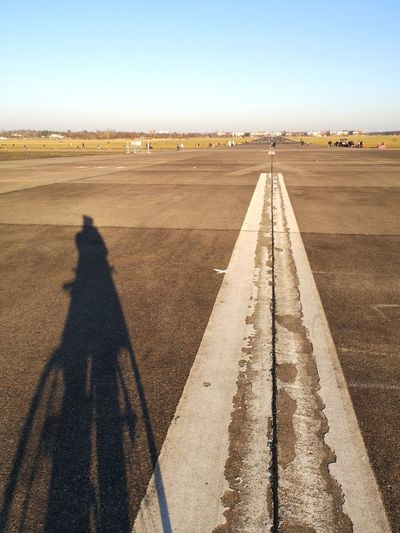 Shadow of person on road
