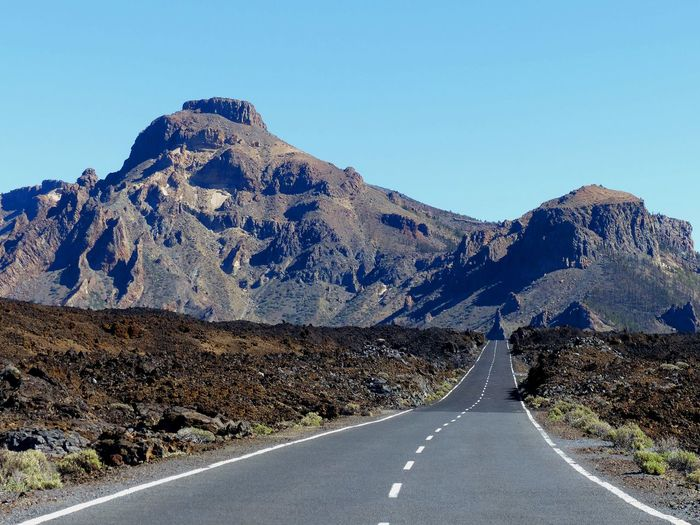 Empty road by mountains against clear sky