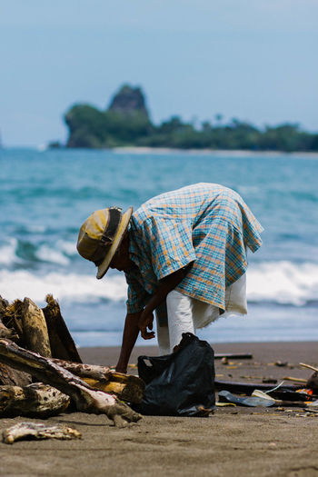 Senior woman picking drift wood at sea shore