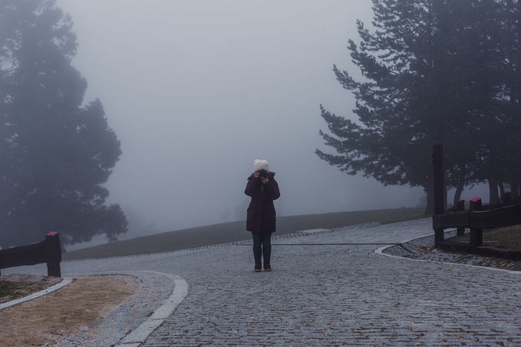 Full length of woman photographing while standing on road during foggy weather