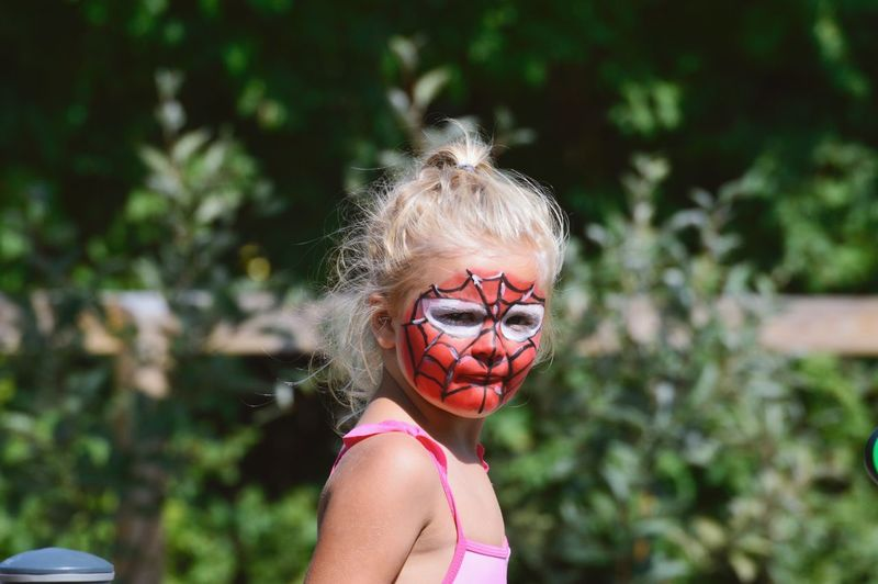 Portrait of girl with painted face standing against plants