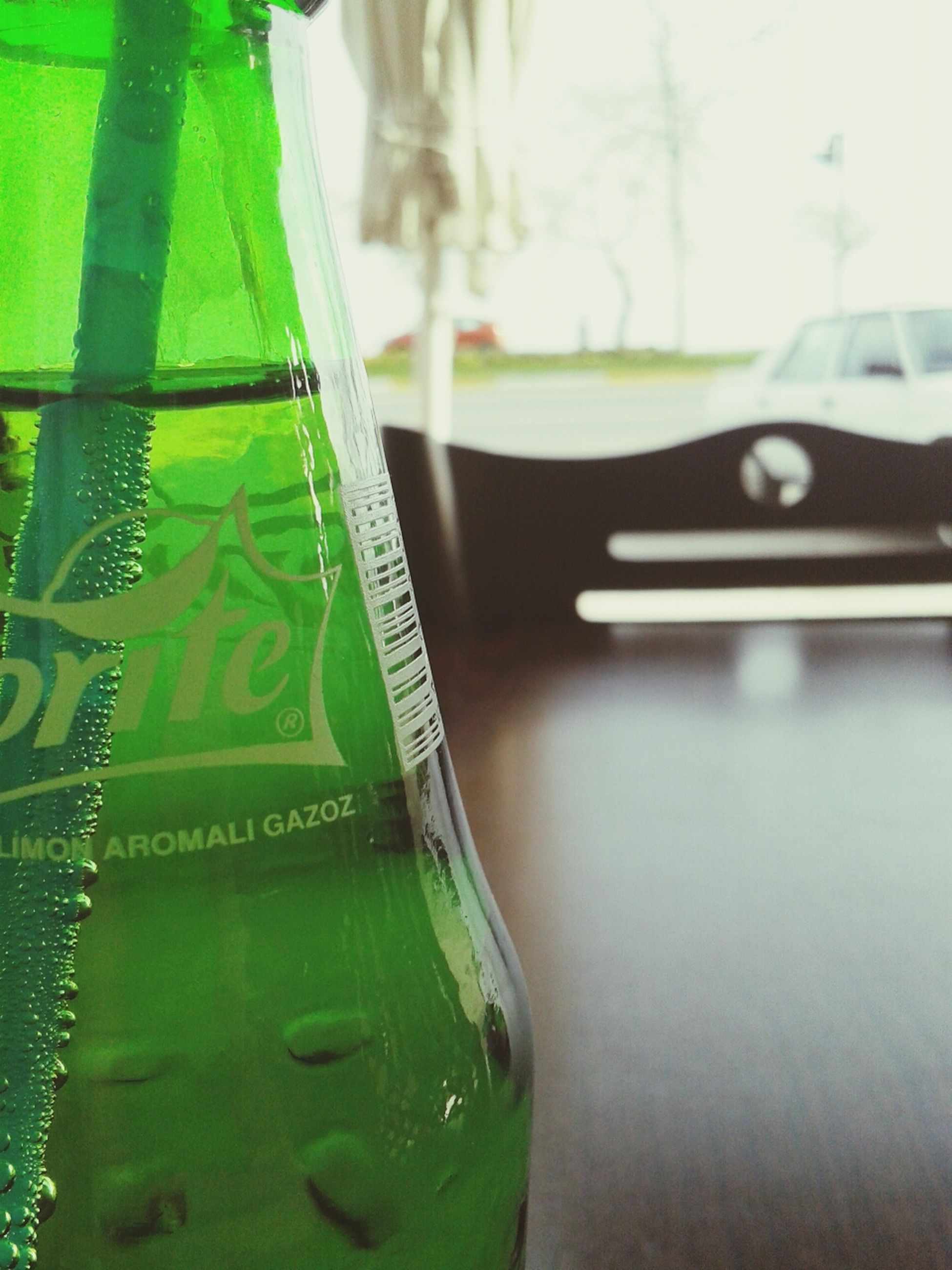 focus on foreground, close-up, transportation, reflection, water, green color, mode of transport, selective focus, car, table, day, indoors, part of, street, land vehicle, glass - material, incidental people, wet, cropped, transparent