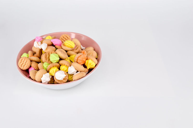 High Angle View Of Multi Colored Cookies In Bowl Against White Background