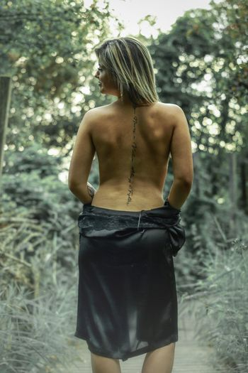 Rear view of backless woman standing against trees
