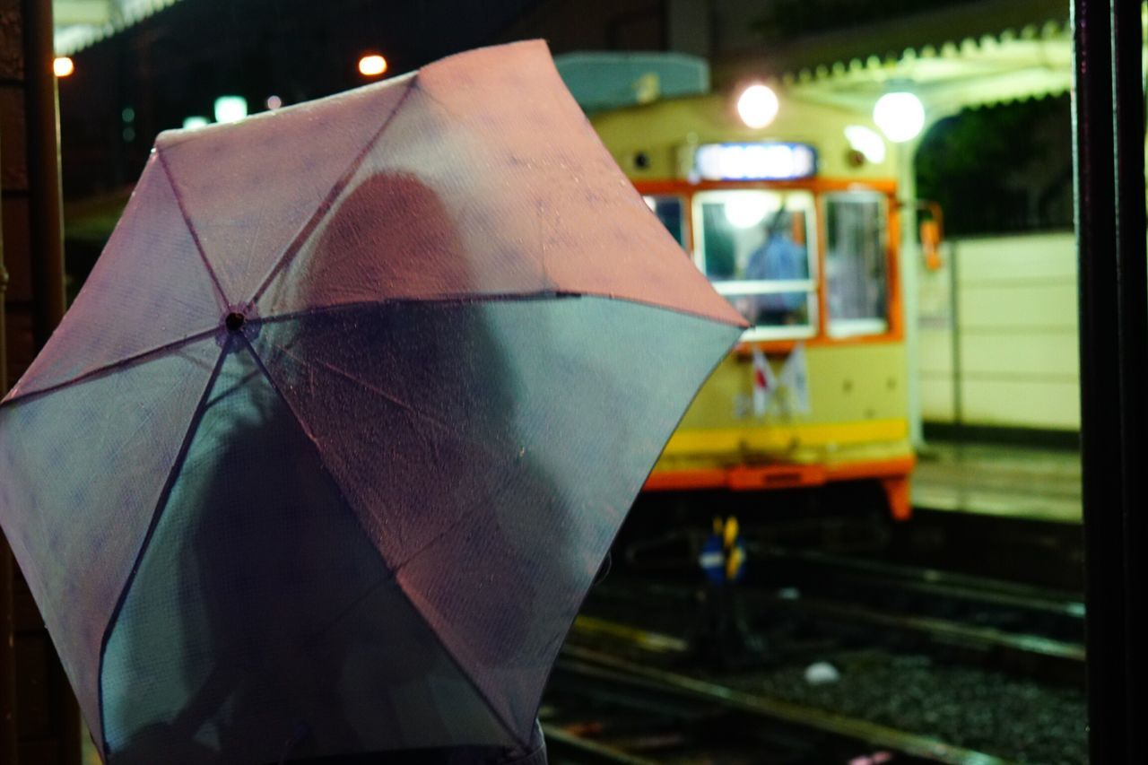 Rear view of woman with umbrella standing at railroad station