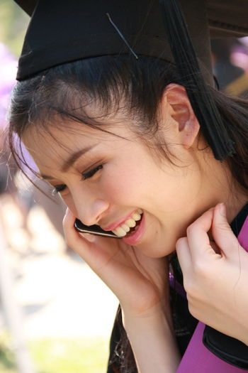 Cheerful young woman talking on smart phone