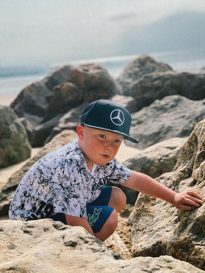 Boy on rock at beach