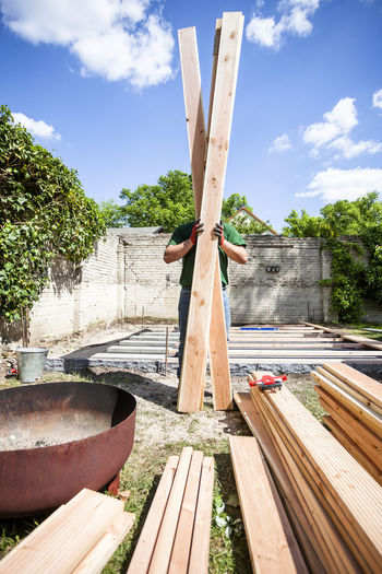 Construction Construction Site DIY Do It Yourself Home Improvement Working Balance Balanced Building Building Site Construction Work Garden Handmade Holding Materials One Person Outdoors Pieces Plank Planks Of Wood Project Real People Timber Tools Wood - Material