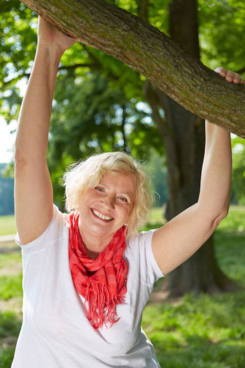 Portrait Of Senior Woman Smiling While Holding Branch At Park