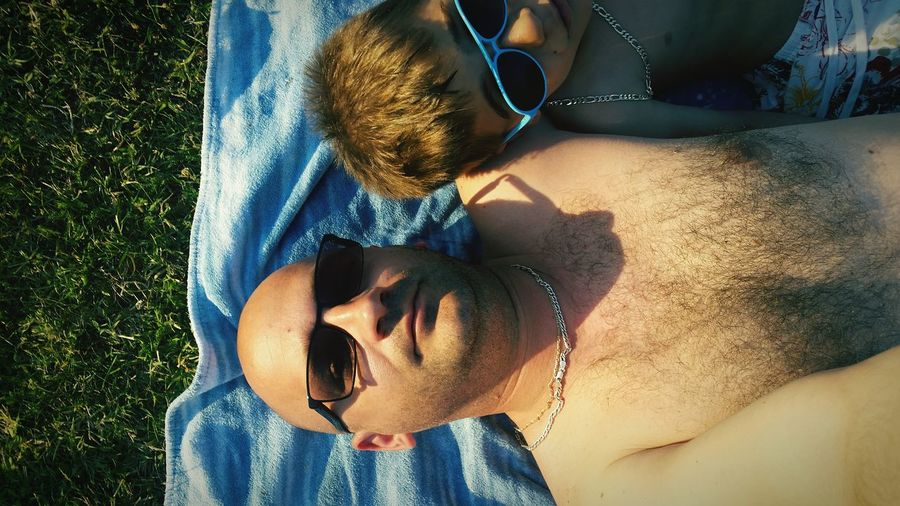 High Angle View Of Father And Son Wearing Sunglasses While Lying On Blanket