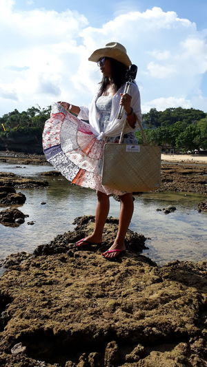 Asian girl wearing a cowboy hat and lifting skirt Reef Rocks Tide Out Shore Water Full Length Women Beach Standing Hat Sky Casual Clothing Straw Hat Fishing Net Sun Hat Ankle Deep In Water Asian Style Conical Hat Sandal Puddle