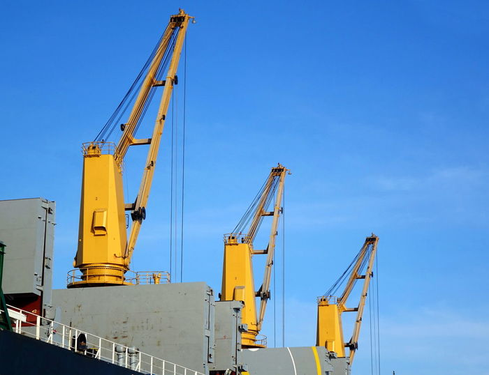 Three loading cranes on a large ocean-going freighter Cargo Ship Harbor Ship Crane Blue Sky Crane - Construction Machinery Dock Freight Transportation Freighter Industry Loading Crane Low Angle View Machinery Pier Transportation