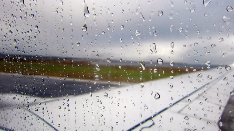 Raindrops on airplane window by the runway. A rainy day on an airport runway. Raindrops falling on the side glass window. AeronauticalEngineer Aircraft Aircraft Wing Airliner Glass Airplane Airplane Window Arrival Aviation Aviationphotography Close-up Defocused Departure Drop Flight Focus On Foreground Grounded Mode Of Transport No People Passenger Conditions Plane Rain RainDrop Runway Transportation Waterdrop
