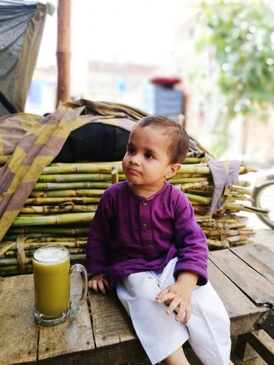 Boy Looking Away While Having Sugar Cane Juice On Wooden Bench