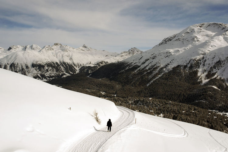 A view of a man walking in the snow covered landscape in the mountains in the alps switzerland Adventure Beauty In Nature Cold Temperature Day Extreme Sports Landscape Leisure Activity Lifestyles Mountain Mountain Range Nature One Person Outdoors Real People Scenics Ski Holiday Sky Snow Snowcapped Mountain Sport Tranquil Scene Tranquility Vacations White Color Winter
