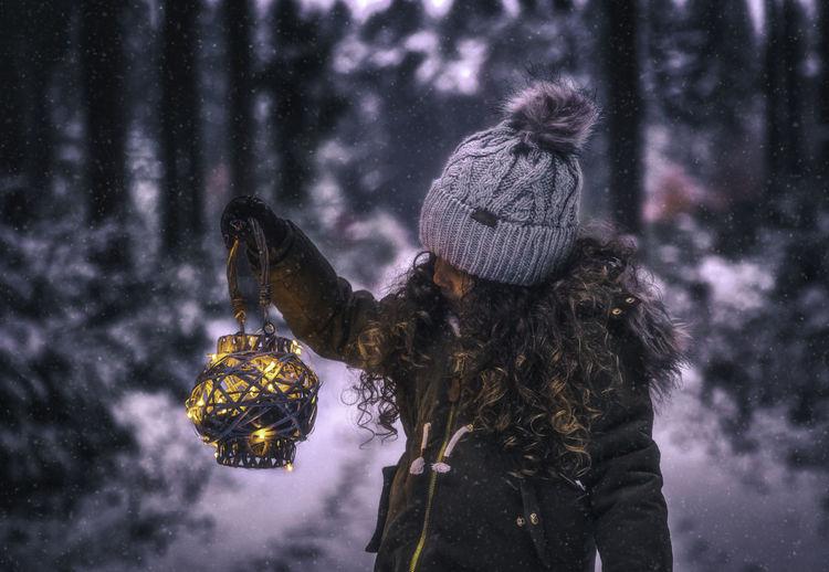 Girl In Warm Clothing Holding Illuminated Lantern