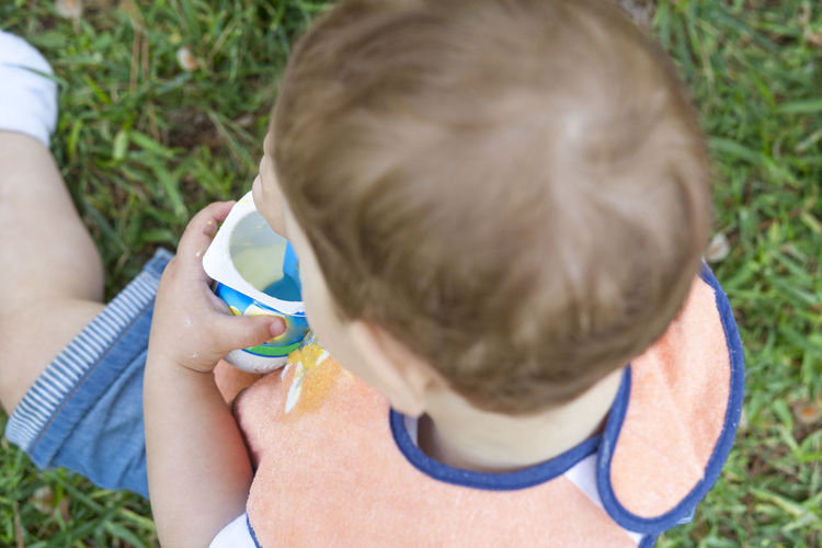 High angle view of boy eating yogurt while sitting on grassy field