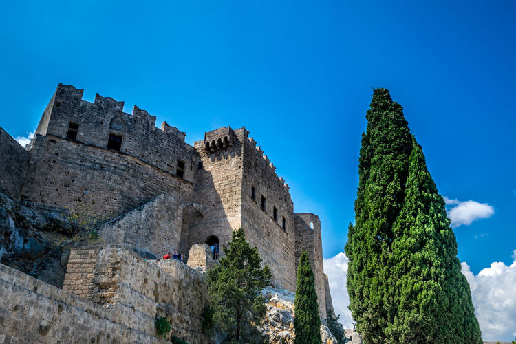 Low angle view of castle in lindos by tree against blue sky