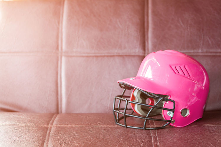 Close-up of pink sports helmet on brown sofa