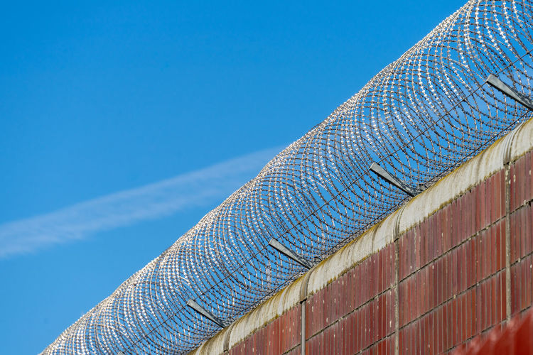 Barbed Wire Protection Security Secure Jailhouse Jail Prison Fence Wall - Building Feature Blue No People Sky Pattern Built Structure Architecture Low Angle View Day Copy Space Nature Roof Sunlight Clear Sky Outdoors Close-up Metal Building Exterior Textured  Textile