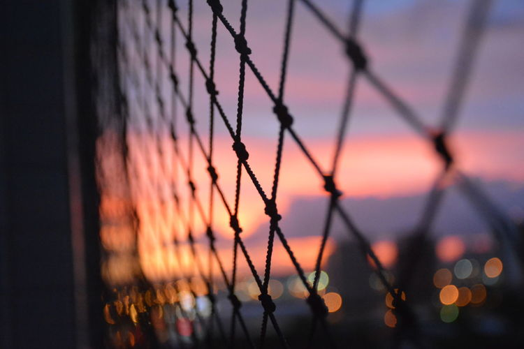 Close-Up Of Chainlink Fence Against Sky At Sunset