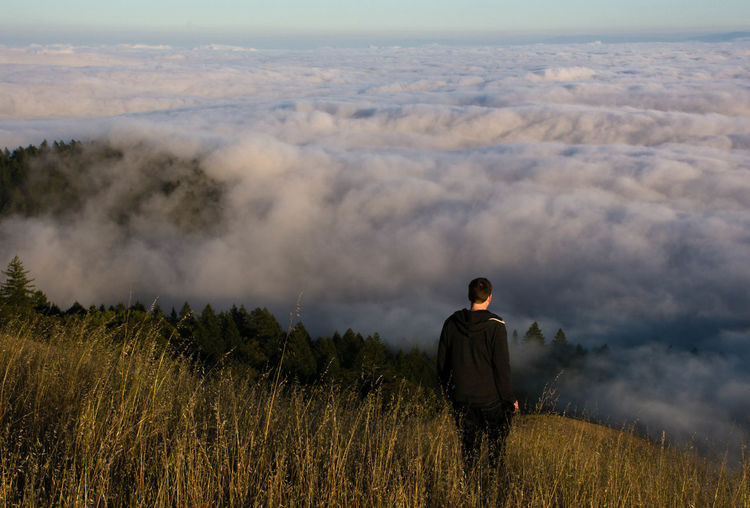 High Angle View Of Man Standing On Mountain Against Cloudscape