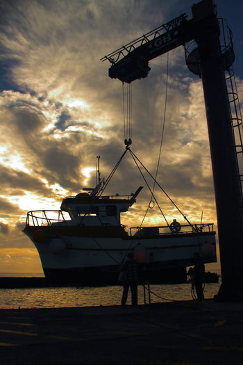 Backlit Boat Backlit Boat Cloud - Sky Dramatic Sky Fishing Boat Harbor Hoisting Hoisting Crane Outdoors Quayside Sky Sunrise Sunrise And Clouds Sunrise Silhouette Sunset Suspended In Air Two Is Better Than One