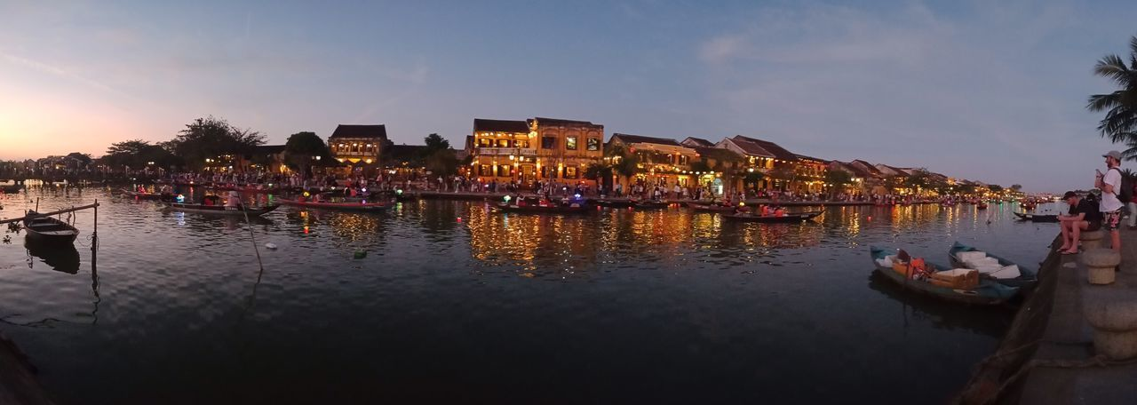 Boats in lake against illuminated buildings in background
