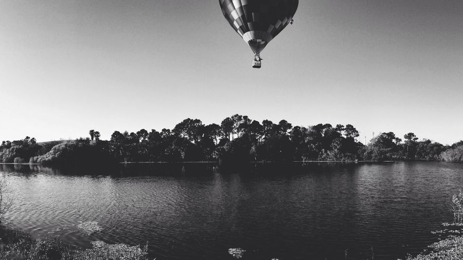 Parachute Flying Over Calm Lake In Forest
