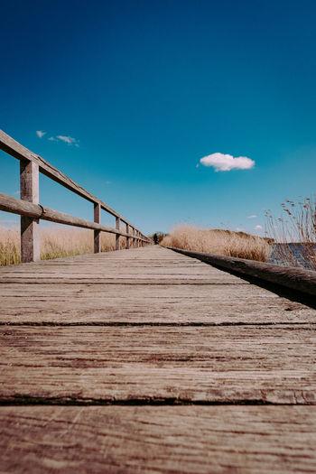 Surface level of boardwalk against blue sky