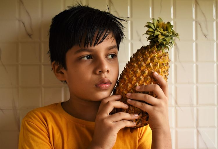 Portrait of boy holding pineapple
