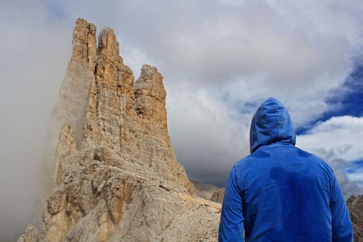 Rear view of man looking at rock formation against cloudy sky