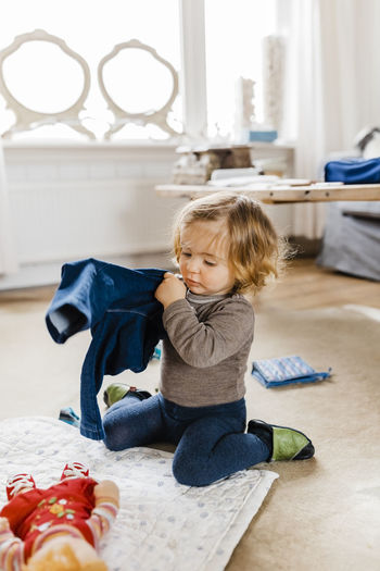 Cute girl holding clothes while sitting on floor at home
