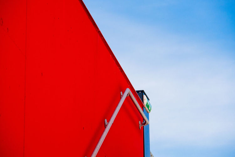 Low angle view of railing on red wall against sky
