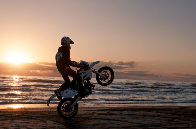 Beach Beauty In Nature Biker Extreme Sports Headwear Helmet Horizon Over Water Lifestyles Men Motorcycle One Person Outdoors Riding Sea Sky Sport Sunset Transportation