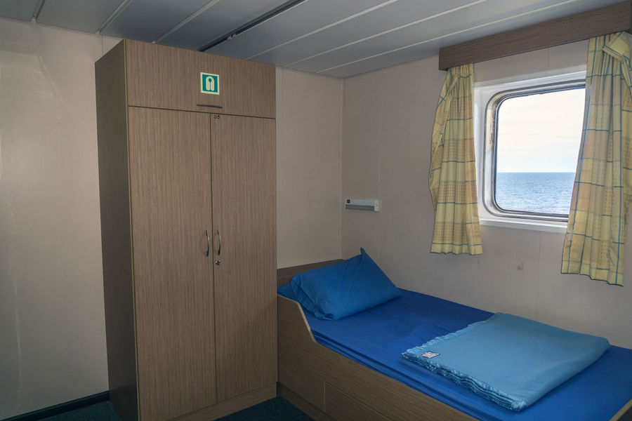 a cabin with sea view Blanket Linen Client Seaman Cabin Mattress Bed Window Glass Offshore Offshore Life Maritime Nautical Closet Door Curtain Bedsheets Pillow Sleep Rest Blue Sea View Sea Horizon Over Water Room Single Barge Construction Business Finance And Industry Door